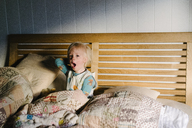 Portrait of boy yawning while sitting on bed at home - CAVF31663