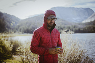Hiker in hood holding drink can while standing by lake at Grand Teton National Park - CAVF31759