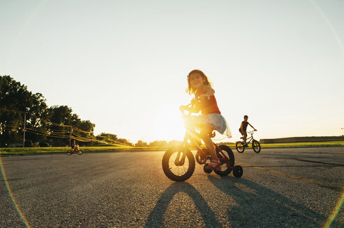 Siblings riding bicycle on road at park against clear sky - CAVF31777