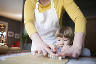 Midsection of mother assisting son cutting dough with pastry cutters in kitchen - CAVF31828