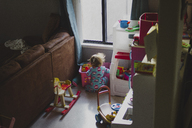 High angle view of girl playing with toys at home - CAVF31831
