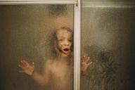 Portrait of girl in shower seen through glass - CAVF31834