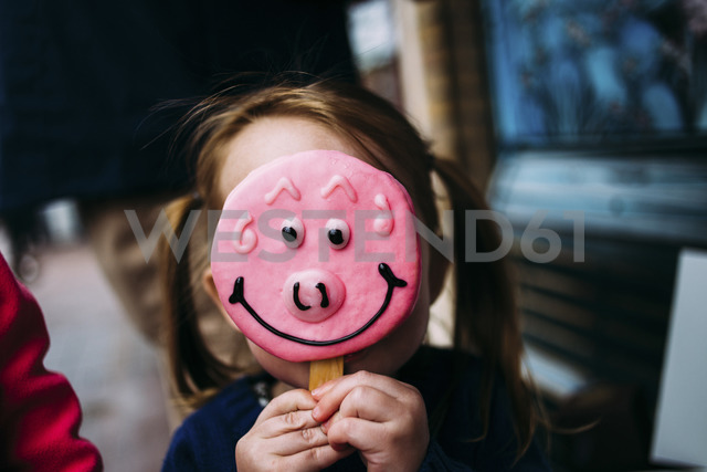 Close-up of girl hiding face with candy - CAVF31840