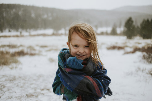 Portrait of happy girl wrapped in blanket during winter - CAVF31852