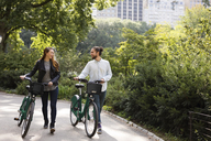 Couple talking while walking on footpath with bicycles - CAVF31876