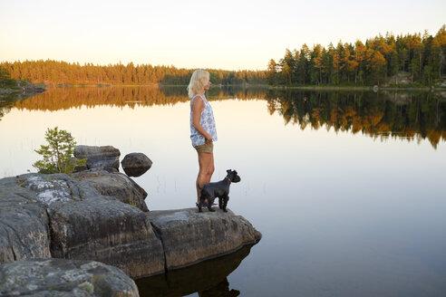 Woman and dog looking at view at lake side - FOLF06021