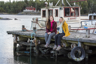 Teenage girl sitting with young woman on jetty - FOLF06039