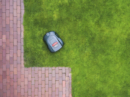 Germany, Bavaria, robotic lawn mower on meadow - MMAF00325