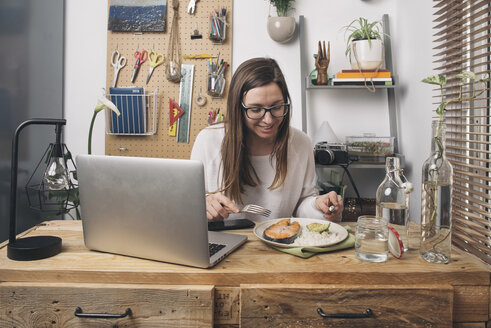 Woman having lunch at wooden table with laptop - SKCF00378