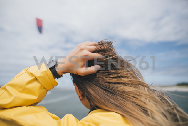 France, Brittany, Landeda, Dunes de Sainte-Marguerite, rear view of long-haired young woman at the coast - GUSF00590