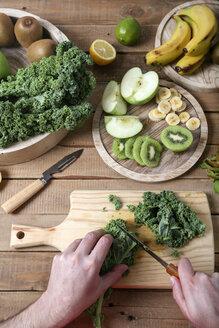Man preparing green smoothie cutting kale - RTBF01123