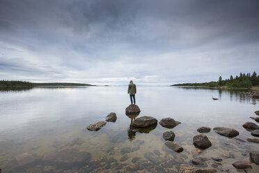 Man standing on rock by a lake - FOLF06379