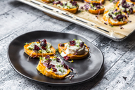 Slices of sweet potato with cream cheese, ramson cream, goat cheese, cress and cranberries - SARF03646