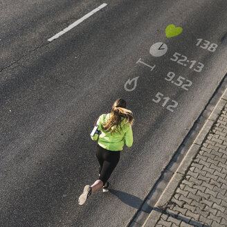 Young woman running on a street with data - UUF13176