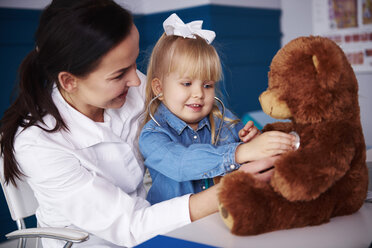 Doctor and girl examining teddy in medical practice - ABIF00214