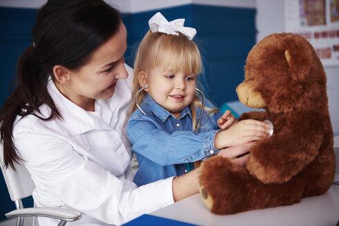 Doctor and girl examining teddy in medical practice - ABIF00214