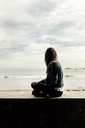 Young woman sitting on a wall looking at the sea - MGOF03747