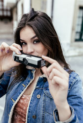 Portrait of a brunette woman with an old camera in a town - MGOF03753
