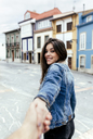 Portrait of a smiling brunette woman holding hand in a town - MGOF03756