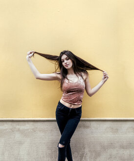 Portrait of a beautiful brunette woman in front of a wall - MGOF03759