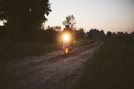 Male biker riding motorcycle on dirt road against clear sky during sunset - CAVF32165
