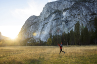 Cheerful woman running on grassy field at Yosemite National Park - CAVF32267