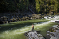 Rear view of man standing on rock in Stillaguamish river - CAVF32285