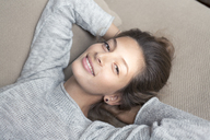 Portrait of smiling woman lying on couch - PNEF00579