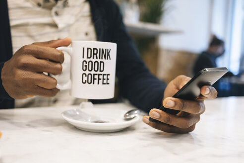 Close-up of man with cup of coffee in a cafe using cell phone - MAUF01361