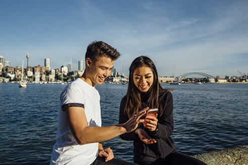 Happy young couple using smart phone while exercising on promenade against Sydney Harbour Bridge - CAVF32325