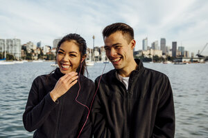 Happy young couple listening music while exercising against cityscape - CAVF32328