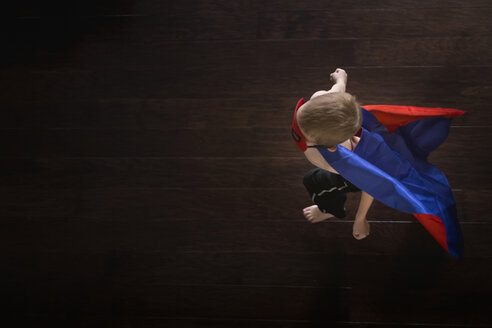 Overhead view of boy wearing superhero cape while walking on hardwood floor - CAVF32370