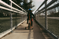 Rear view of boy riding bicycle on footpath amidst fences - CAVF32382