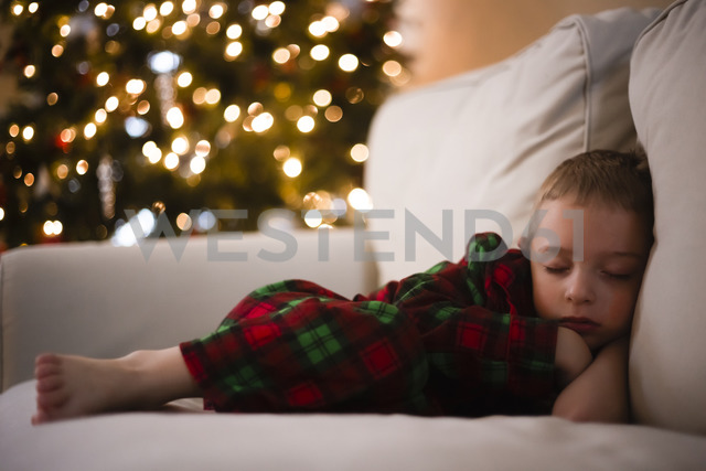 Full length of boy sleeping on sofa during Christmas - CAVF32385