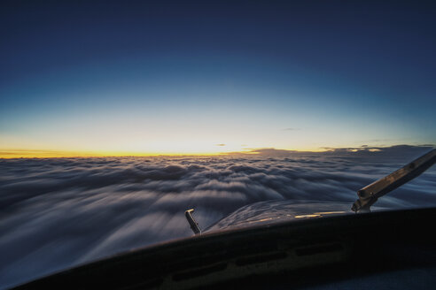 Airplane flying over cloudscape seen through windshield during sunset - CAVF32397