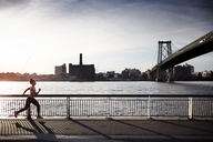 Determined woman jogging on promenade with Williamsburg Bridge in background - CAVF32454