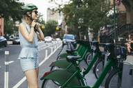 Smiling woman wearing helmet while standing by bicycles on street - CAVF32493