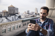 Smiling man using smart phone while sitting in balcony against sky - CAVF32553