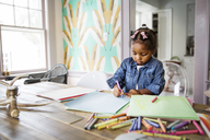 Cute girl coloring with crayon in book on table at home - CAVF32673