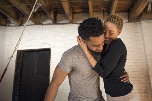 Happy couple embracing in bedroom - CAVF32706