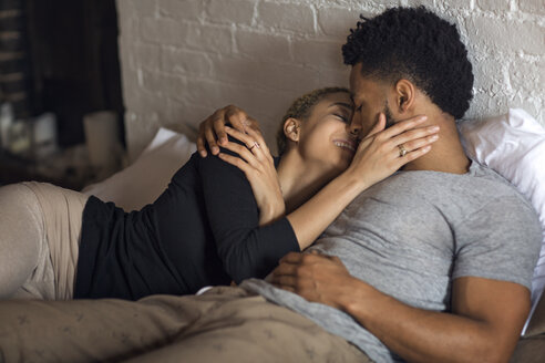 Romantic young couple lying on bed at home - CAVF32712
