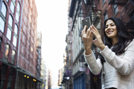 Happy young woman photographing through smart phone in city - CAVF32772