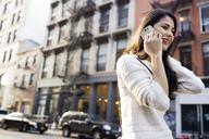 Happy woman answering smart phone on city street - CAVF32787