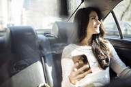 Thoughtful woman holding smart phone while looking through taxi window - CAVF32802