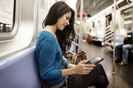 Side view of woman using tablet computer in train - CAVF32814