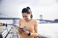 Happy female athlete listening music through smart phone with Williamsburg Bridge in background - CAVF32847