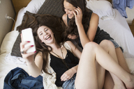 High angle view of cheerful female friends taking selfie while relaxing on bed at home - CAVF33012