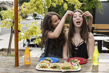 Cheerful friends playing with food while sitting at sidewalk cafe - CAVF33018
