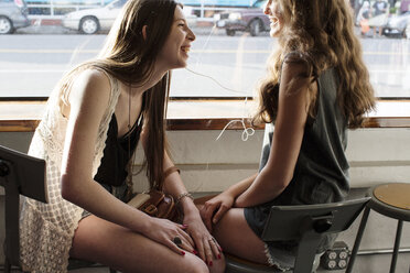 Smiling female friends listening music while sitting in cafe - CAVF33024