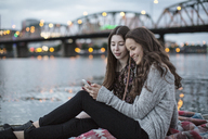 Smiling female friends using smart phone while sitting on pier against Burlington Northern Railroad Bridge 9.6 - CAVF33036